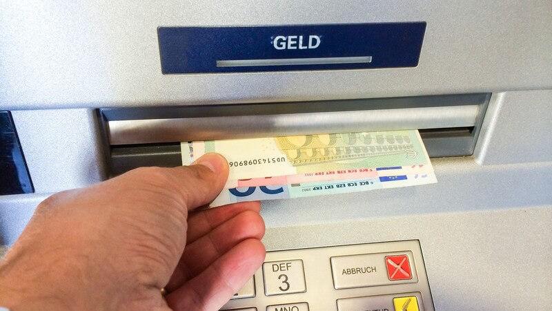 Mann nimmt Geldscheine aus einem Bankautomaten