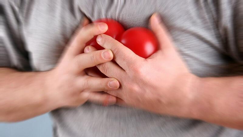Körperausschnitt Mann drückt sich rotes Plastikherz an die Brust