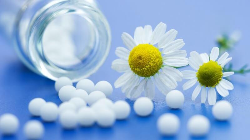 Homöopathie - Medikamentenglas und weiße Kügelchen mit zwei Gänseblümchen auf blauem Untergrund