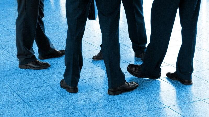 Vier Paar Beine von Geschäftsmännern im Anzug
