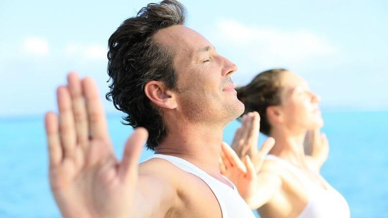 Paar in weißen Oberteilen macht Yoga-Übungen am Meer
