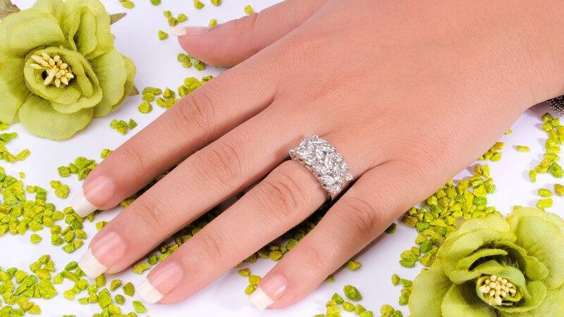 Hand mit langen, gepflegten Fingernägeln und funkelndem Ring liegt neben einer grünen Blüte