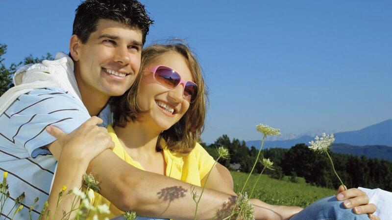 Junges Paar sitzt auf Bergwiese, er umarmt sie von hinten, beide lächeln