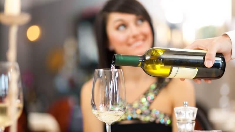 Kellner im Restaurant schenkt einer Dame ein Glas Weißwein ein, sie blickt freundlich zu ihm hoch