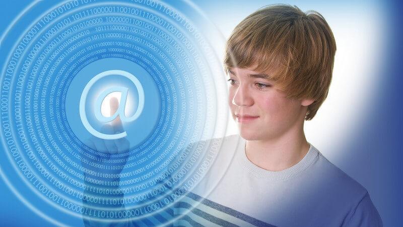 Jugendlicher vor blauem Hintergrund tippt mit dem Finger auf ein imaginäres E-Mail-Zeichen (@-Zeichen)