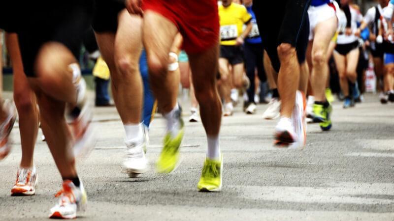Beine und Füße von Marathonläufern auf grauem Asphalt