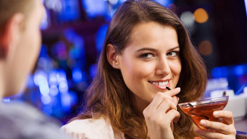 Braunhaarige Frau fasst an den Strohhalm ihres Cocktails und wirft einem Mann einen verführerischen Blick zu