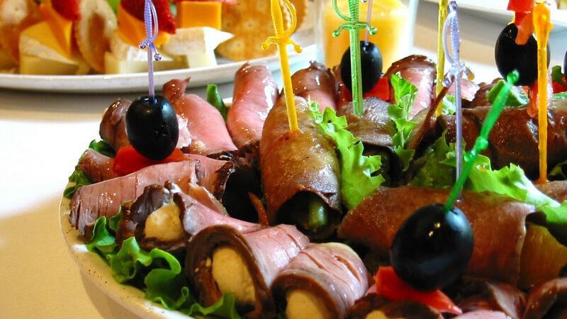 Essen - Kleine Fleischhäppchen mit Olive und Pieker auf Buffet-Teller