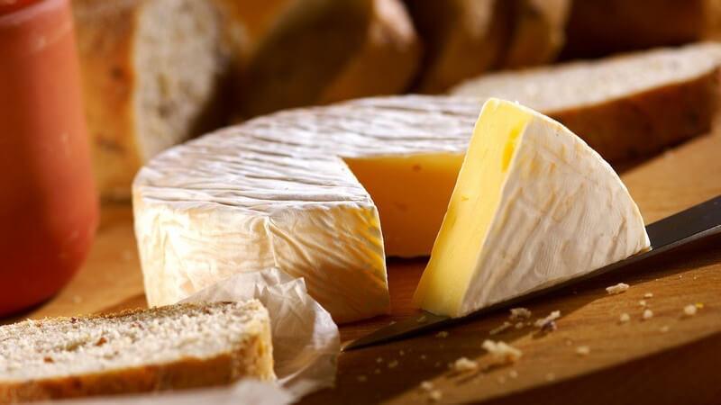 Runder ganzer Käse auf Holzbrett, eine Ecke rausgeschnitten