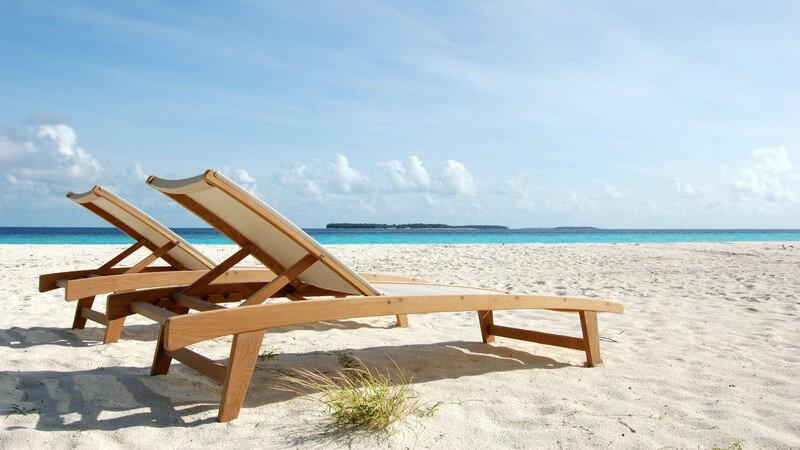 Zwei LIegen aus Holz am leeren Sandstrand, im Hintergrund türkises Meer