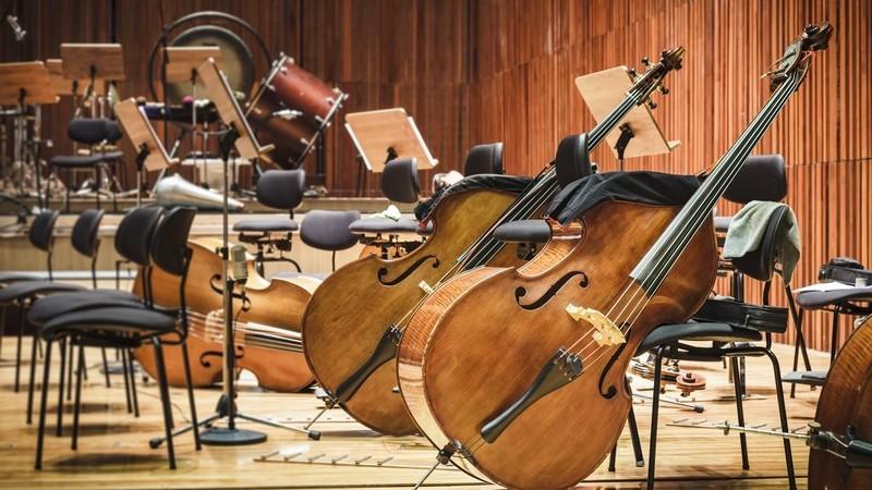 Blick in einen Konzertsaal voller Instrumente und Stühle für die Musiker, vorne stehen große Celli