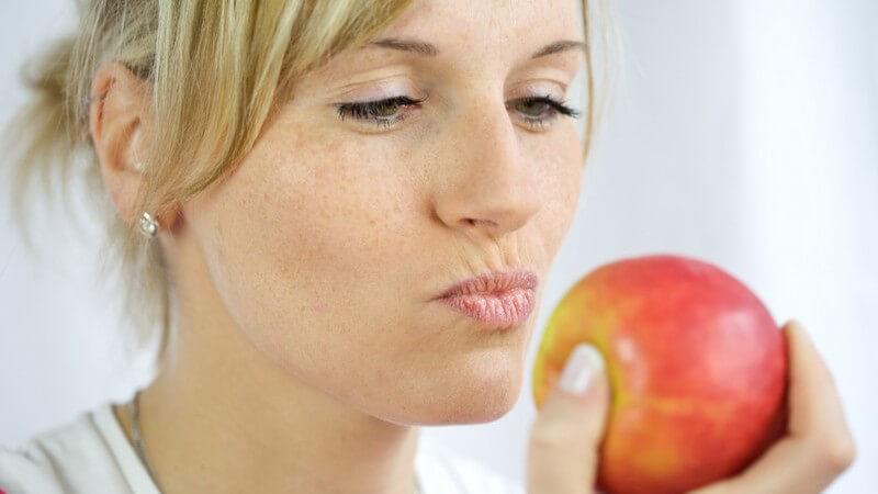 Blonde Frau schaut genüsslich auf roten Apfel