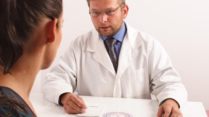 Arzt in weißem Kittel sitzt mit Patientin in der Sprechstunde