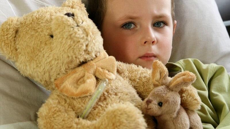 Kind liegt mit Teddy im Arm krank im Bett