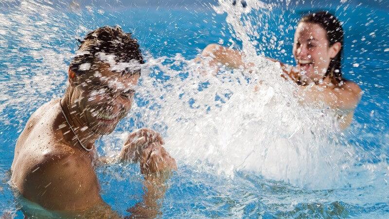 Paar im Swimmingpool, sie spritzt ihn mit Wasser voll