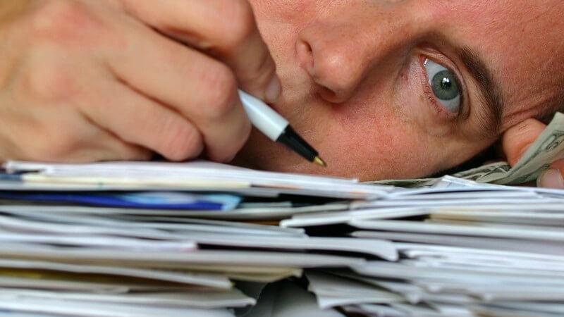 Überforderter Geschäftsmann hat Kopf auf Stapel Papieren liegen
