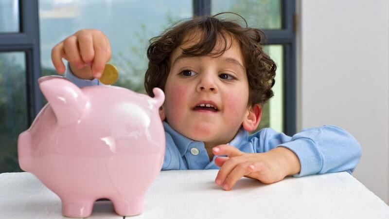 Kleiner Junge wirft Münze in rosanes Sparschwein