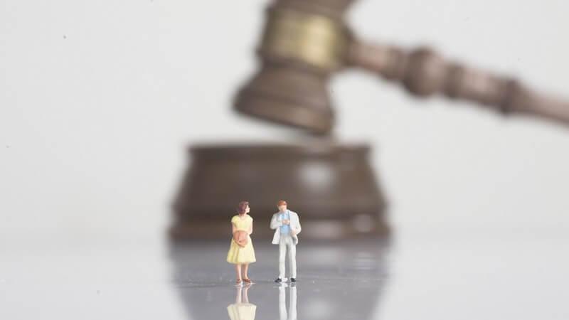 Kleine Figuren Mann und Frau vor riesigem Richter Hammer