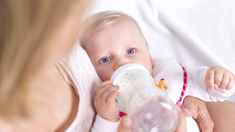 Blondes Baby mit Lätzchen liegt bei der Mutter im Arm und trinkt aus einem Fläschchen