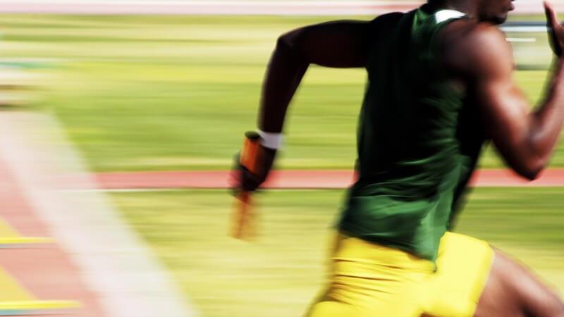 Staffellauf, dunkelhäutiger Sportler rennt mit Staffelstab über Sportplatz, Sprint