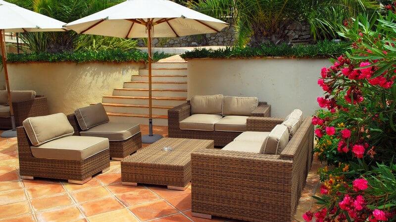 Terrasse mit weiß-braunen Gartenmöbeln und Sonnenschirm vor einer weißen Mauer mit Treppe