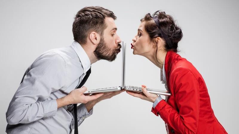 Mann und Frau in Businesskleidung stehen sich mit ihren Laptops direkt gegenüber und küssen jeweils ihren Bildschirm