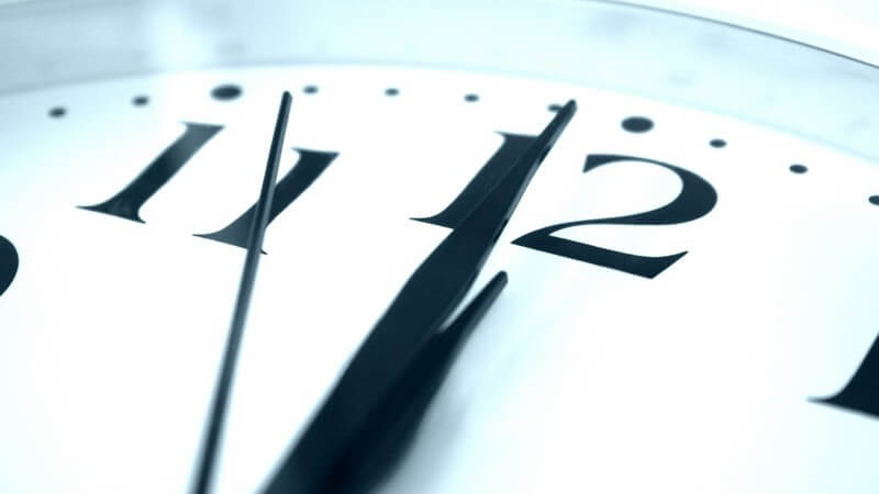 Nahaufnahme weiße Uhr mit schwarzem Ziffernblatt zeigt vier Sekunden vor Zwölf