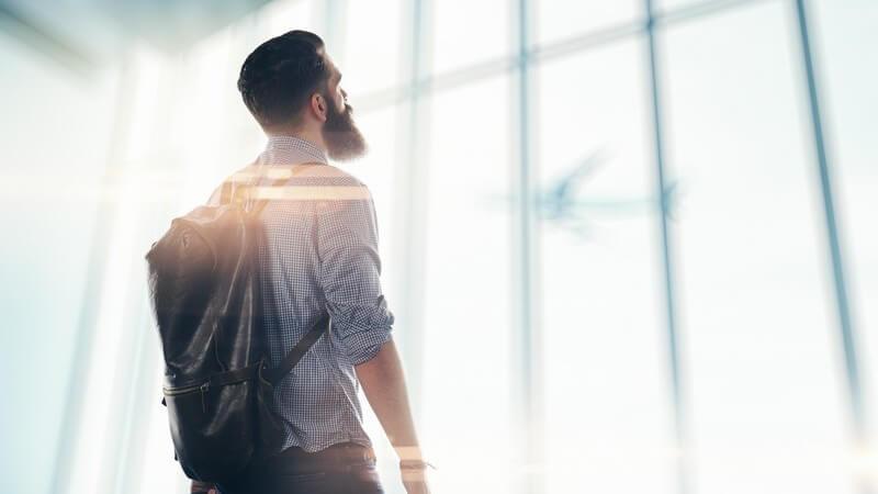 Bärtiger Mann steht mit Koffer und Rucksack am Flughafen und blickt nach draußen