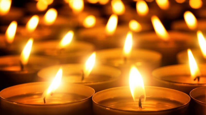 Ein Meer an brennenden Kerzen in der Dunkelheit