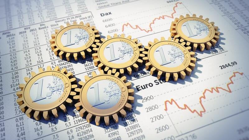 Sechs Ein-Euromünzen im Zahnrad-Look liegen verzahnt auf einem Papier mit Börsen- und Währungskursen