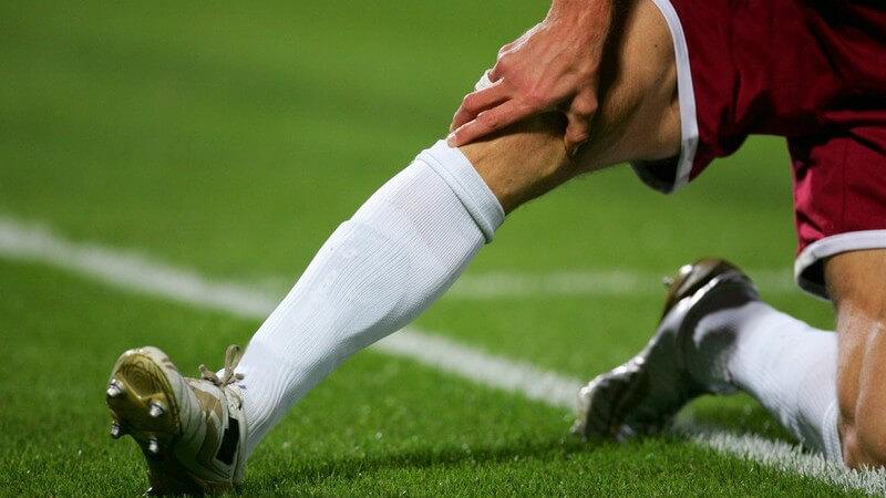 Nahaufnahme Beine eines Fußballers auf Fußballfeld