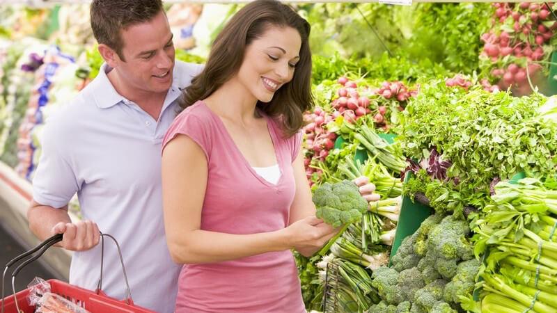 Junges Paar beim Einkaufen im Supermarkt in Gemüseabteilung