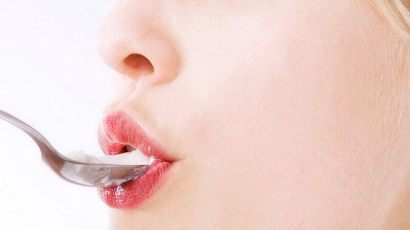 Junge Frau isst genüsslich Eiscreme vom Löffel