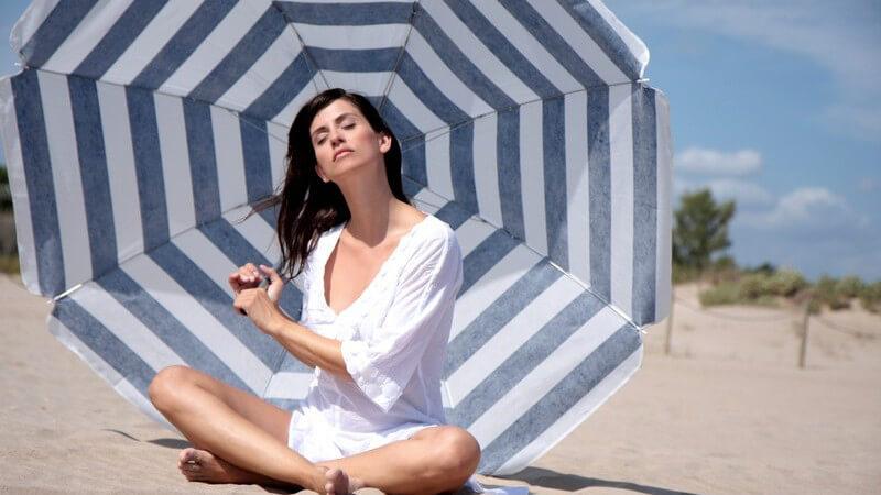Frau sitzt mit Sonnenschirm am Strand