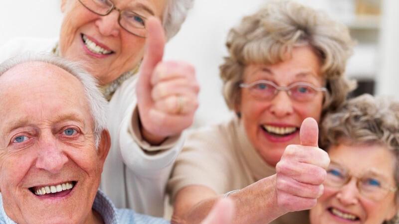 Gruppe alter Menschen lacht in Kamera, zeigen Daumen nach oben