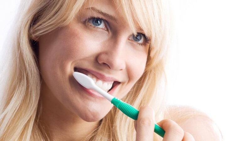 Junge Frau beim Zähneputzen, weißer Hintergrund