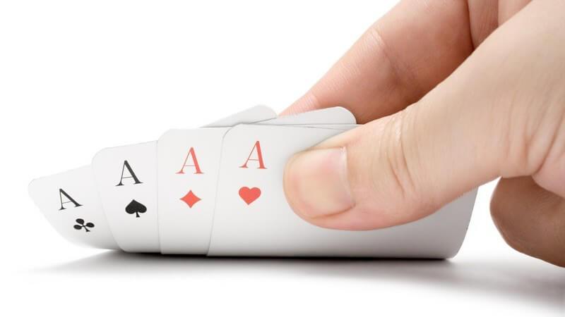 Hand deckt 4 Karten mit Assen halb auf