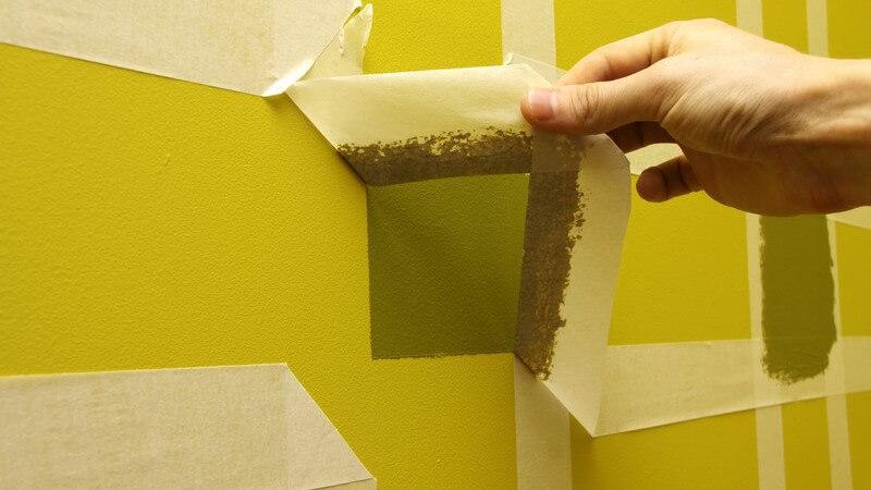Kreppband wird nach Streichen von Wand gezogen