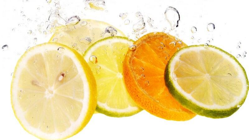 Scheiben von Zitrusfrüchten werden ins Wasser geworfen, bilden Luftbläschen
