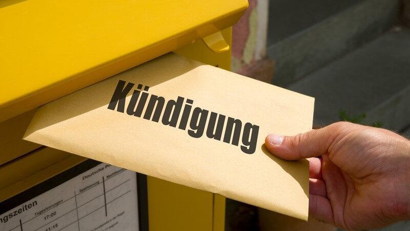 """Hand wirft einen Brief mit der großen Aufschrift """"Kündigung"""" in einen gelben Post-Briefkasten"""
