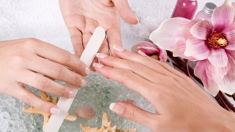 Frau bei Maniküre, Nägel der rechten Hand werden mit Nagelfeile gefeilt