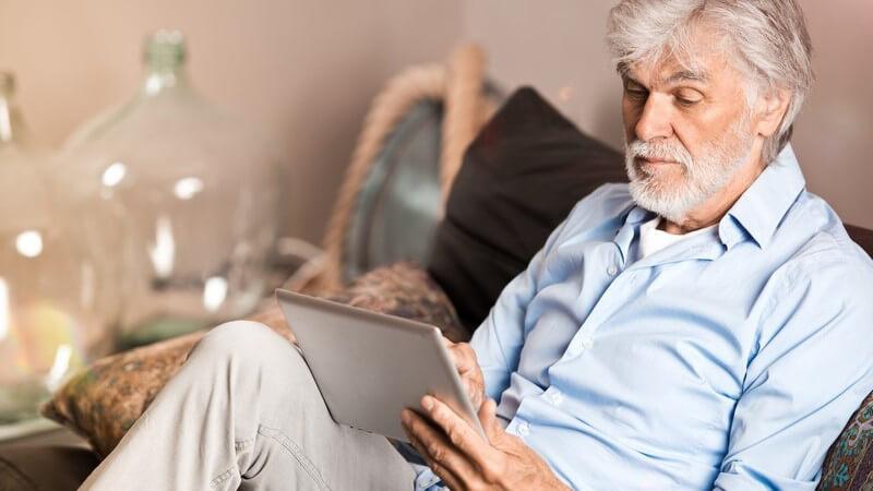 Älterer Herr mit grauen Haaren und Vollbart sitzt in blauem Hemd mit Tablet-Computer auf der Couch