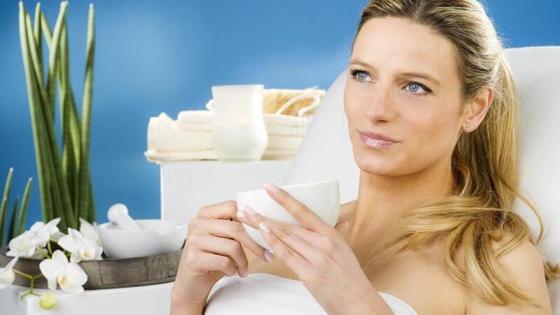 Junge Frau auf weißer Liege in Handtuch entspannt und hält Becher fest