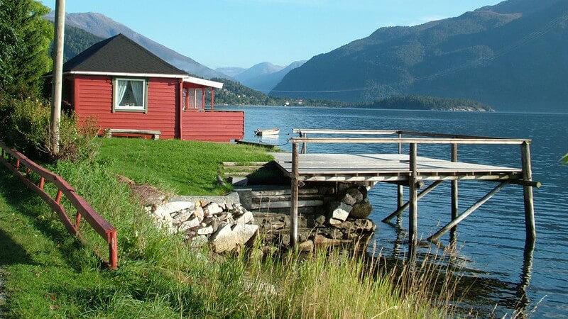 Rotes Häusschen und kleiner Bootssteg an einem norwegischen Fjord