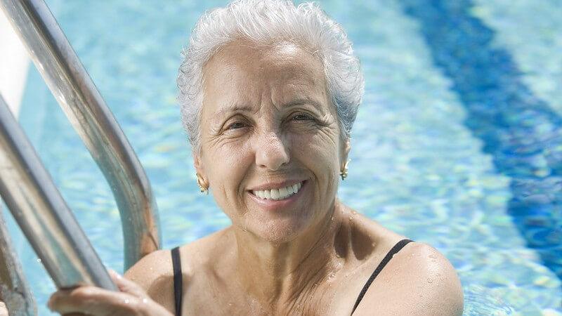 Ältere, lächelnde Frau im Schwimmbecken