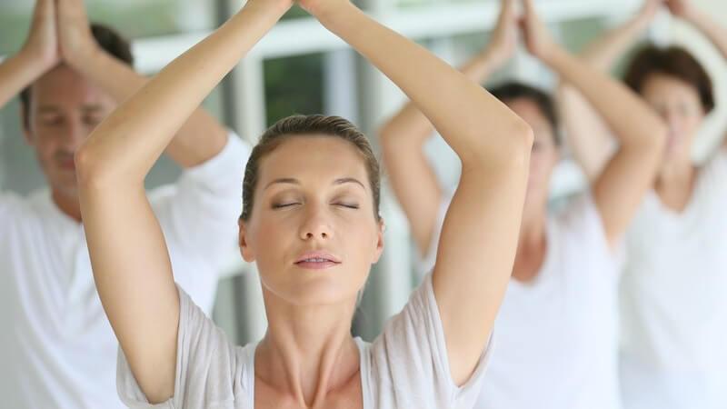 Hübsche Frau macht mit einer Gruppe Yoga-Übungen, alle tragen weiße Kleidung und haben die Augen geschlossen