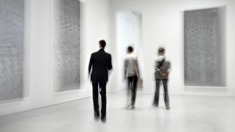 Elegant gekleidete Menschen in einer Kunstgalerie betrachten Bilder