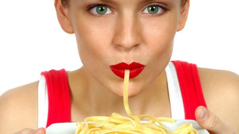Frau mit rotem Lippenstift hält einen Pastateller hoch und saugt an einer Nudel