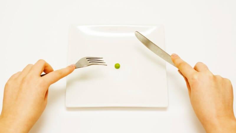 Diät - Zwei Hände mit Messer und Gabel an Teller, auf Teller liegt eine Erbse