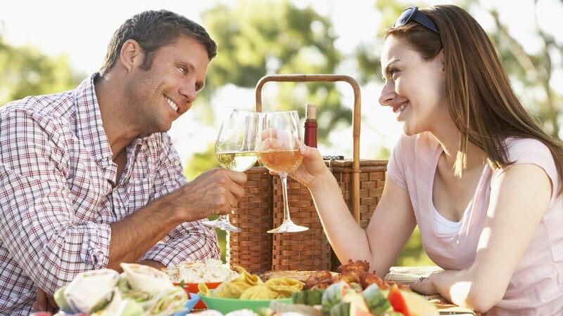 Paar draußen beim Picknick mit Weingläsern